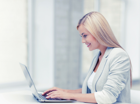 typing: picture of smiling businesswoman using her laptop computer Stock Photo