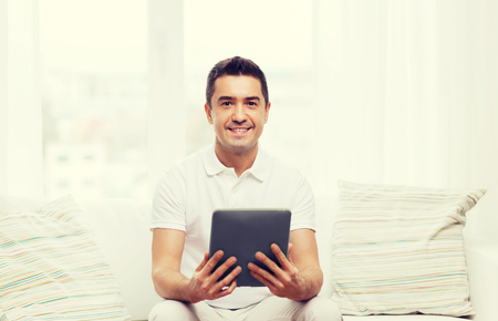 mid distance: technology, people and lifestyle, distance learning concept - happy man working with tablet pc computer at home