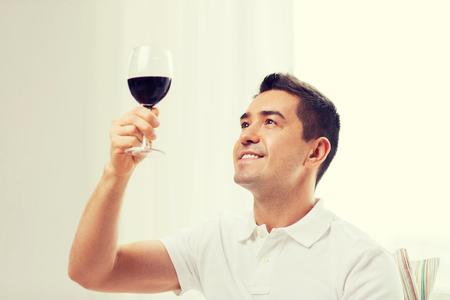 tomando vino: profesión, las bebidas, el ocio y el concepto de la gente - hombre feliz bebiendo vino tinto de vidrio en el hogar Foto de archivo