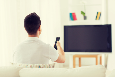 changing channels: leisure, technology, mass media and people concept - man watching tv and changing channels at home from back Stock Photo