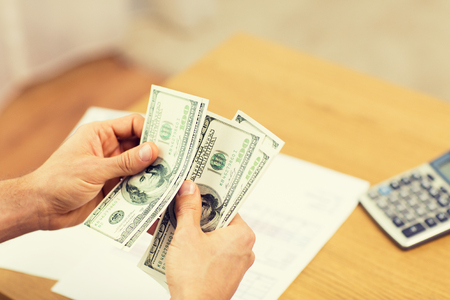 home finances: savings, finances, economy and home concept - close up of man hands counting money at home Stock Photo