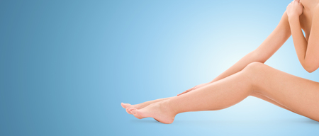 people, beauty, health and body care concept - close up of naked woman legs over blue background photo