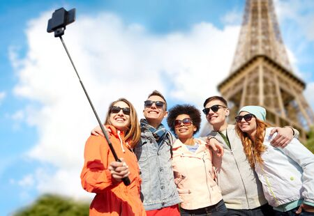 young guy: tourism, travel, people, leisure and technology concept - group of smiling teenage friends taking selfie with smartphone and monopod over paris eiffel tower background