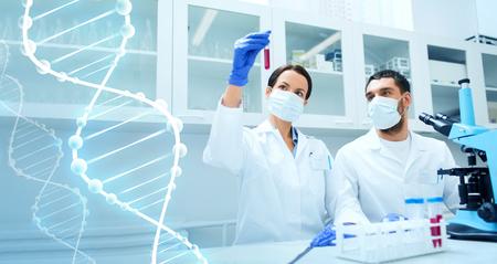microscopio: ciencia, química, la tecnología, la biología y la gente concepto - jóvenes científicos con tubo de ensayo y microscopio haciendo investigación en laboratorio clínico
