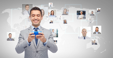 network people: business, people and technology concept - happy businessman texting or reading message on smartphone over gray world map and network contacts background