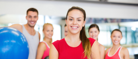 sport fitness: fitness, sport, training, gym and lifestyle concept - smiling woman standing in front of the group of people in gym
