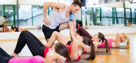 Fitness, Sport, Training, Fitness und Lifestyle-Konzept - Gruppe von lächelnden Frauen mit männlichen Trainer Handeln sitzt, ups auf Matten in der Turnhalle