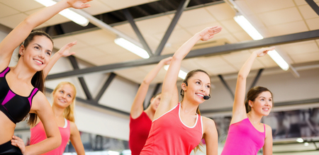 warm up exercise: fitness, sport, training, gym and lifestyle concept - group of smiling people stretching in the gym Stock Photo