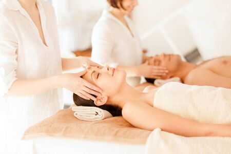 beauty resort: health and beauty, resort and relaxation concept - couple in spa salon getting facial massage