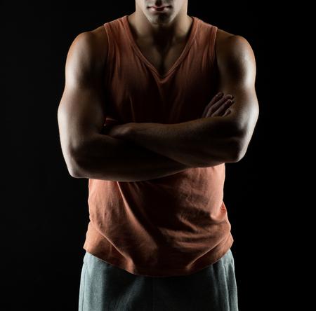 Sport, Bodybuilding, Kraft und Menschen Konzept - junger Mann, der auf schwarzem Hintergrund
