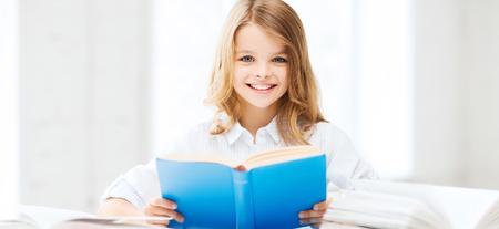jovenes estudiantes: la educación y la escuela concepto - niña estudiante estudiando y leyendo el libro en la escuela Foto de archivo