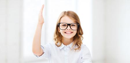 preguntando: la educación y la escuela concepto - niña estudiante que estudia y que levanta la mano en la escuela