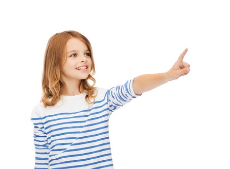 buttons: education, school and virtual screen concept - cute little girl pointing in the air or virtual screen