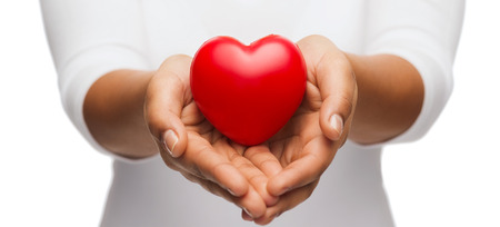 life giving birth: people, relationship and love concept - close up of womans cupped hands showing red heart