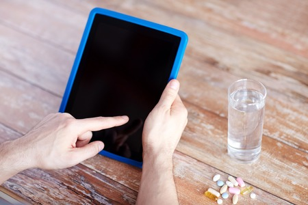 animal body part: medicine, technology, nutritional supplements and people concept - close up of male hands pointing finger to blank tablet pc computer screen, pills and water on table