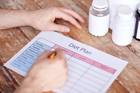 casein: sport, fitness, healthy lifestyle and people concept - close up of man with protein jars writing diet plan at home