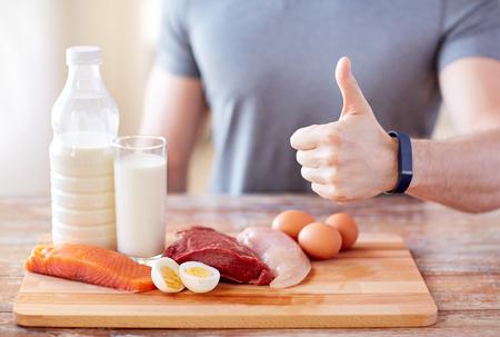 Sport, Fitness, gesunde Lebensweise, Ernährung und Menschen Konzept - Nahaufnahme up des Menschen mit Lebensmittel reich an Protein zeigt Daumen