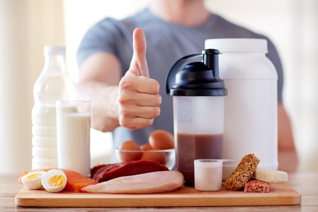 deporte, fitness, estilo de vida saludable, la dieta y el concepto de la gente - cerca del hombre con los alimentos ricos en proteínas que muestra los pulgares para arriba Foto de archivo