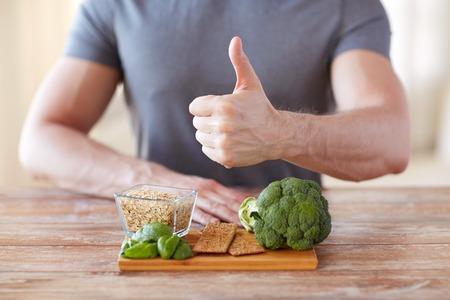 繊維が豊富な食品が親指が表示される男性の手のクローズ アップ健康的な食事、ダイエット、ジェスチャーおよび人々 のコンセプト-