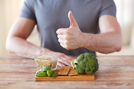 healthy eating, diet, gesture and people concept - close up of male hands showing thumbs up with food rich in fiber Imagens