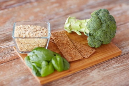 fiber food: healthy eating, diet and fiber rich in food concept - close up of broccoli, crispbread, oatmeal and spinach on wooden table