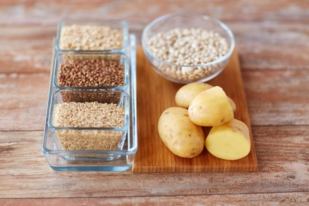 diet, cooking, culinary and carbohydrate food concept - close up of grain and beans in glass bowls with potatoes on table Stock Photo