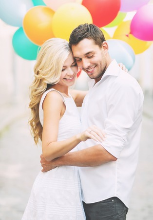 Sommerferien, Feiern und Hochzeit Konzept - Paar mit bunten Luftballons und Verlobungsring