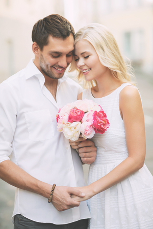 happy couple: summer holidays and dating concept - couple with bouquet of flowers in the city
