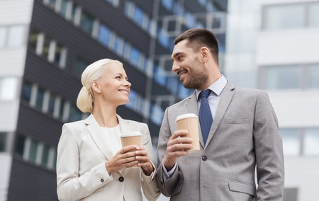 business partnership: business, partnership, hot drinks and people concept - smiling businessmen with paper cups standing over office building