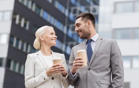 tomando café: negocio, asociación, bebidas calientes y concepto de la gente - hombres de negocios sonriente con vasos de papel se coloca sobre el edificio de oficinas
