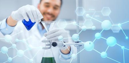la ciencia, la química, la biología, la medicina y la gente concepto - cerca de llenar tubos de ensayo científico con el embudo y en la investigación en laboratorio clínico sobre fondo azul estructura molecular Foto de archivo
