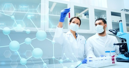 ciencia, química, tecnología, biología y el concepto de la gente - los científicos jóvenes con tubo de ensayo y microscopio en la investigación en laboratorio clínico sobre fondo azul estructura molecular