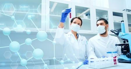 wetenschap, chemie, technologie, biologie en mensen concept - jonge wetenschappers met reageerbuis en microscoop maken van onderzoek in klinisch laboratorium over blauwe moleculaire structuur achtergrond