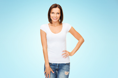 people, advertisement and clothing concept - happy woman in blank white t-shirt over blue background Stock Photo