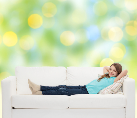 pre teen girls: home, leisure, people and happiness concept - smiling little girl lying on sofa over green lights background