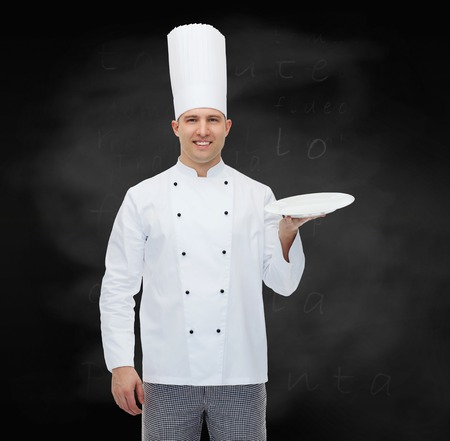 empty of people: cooking, profession, advertisement and people concept - happy male chef cook showing something on empty plate over black chalk board background