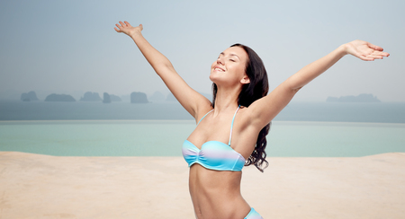woman hands up: people, travel, tourism, happiness and summer concept - happy young woman in bikini swimsuit with raised hands looking up over infinity pool at sea side background