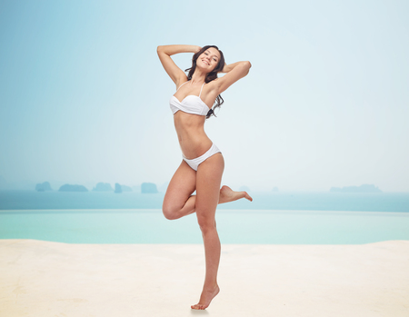 people, fashion, swimwear, summer and beach concept - happy young woman posing in white bikini swimsuit with raised hands and standing on one leg over infinity pool at beach resort