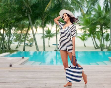 gorgeous girl: people, fashion, summer and beach concept - happy young woman in summer clothes and sun hat with bag over swimming pool at beach resort Stock Photo