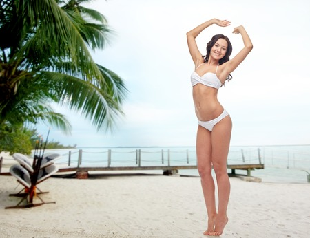 tiptoe: people, swimwear, tourism, travel and summer concept - happy young woman posing in white bikini swimsuit with raised hands over berth on tropical beach background