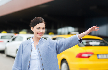 taxis: travel, business trip, people, gesture and tourism concept - smiling young woman waving hand and catching taxi at airport terminal or railway station Stock Photo
