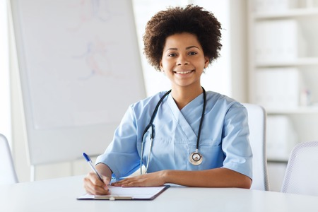 black nurse: medicine, people and healthcare concept - happy female african american doctor or nurse writing medical report to clipboard at hospital