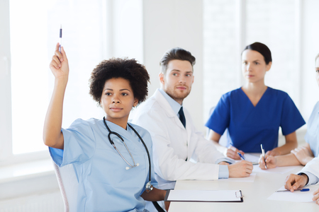 raising: hospital, profession, people and medicine concept - group of happy doctors meeting and asking questions on conference at hospital