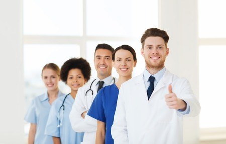 hospital, profession, people and medicine concept - group of happy doctors at hospital showing thumbs up gesture. Stock Photo