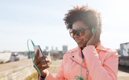 teenagers: technology, lifestyle and people concept - smiling african american young woman or teenage girl with smartphone and headphones listening to music outdoors
