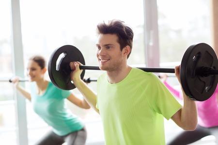 pesas: fitness, deporte, entrenamiento, gimnasio y estilo de vida concepto - grupo de personas que hacen ejercicio con pesas en el gimnasio