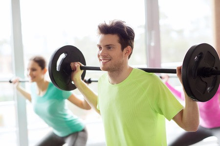 warm up exercise: fitness, sport, training, gym and lifestyle concept - group of people exercising with barbell in gym