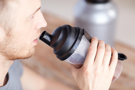 whey: sport, fitness, healthy lifestyle and people concept - close up of man with jar and bottle drinking protein shake