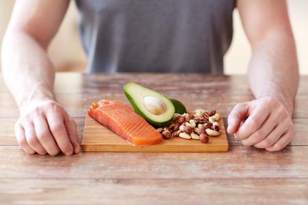 hombre comiendo: estilo de vida saludable, la dieta y el concepto de la gente - cerca de las manos masculinas con alimentos ricos en proteínas en la tabla de cortar en la mesa