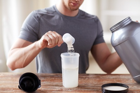 drinks: sport, fitness, healthy lifestyle and people concept - close up of man with jar and bottle preparing protein shake